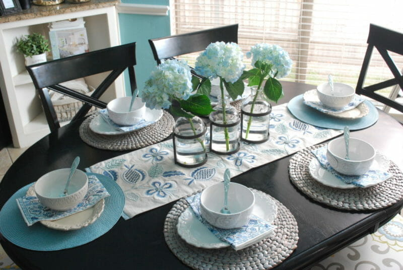 Blue and white tablescape using mismatached dishes with metal and glass floral vase for centerpiece