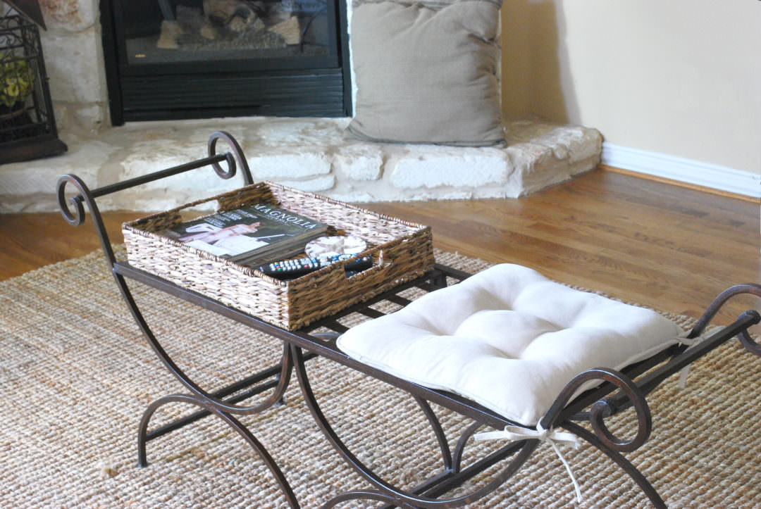iron bench used for coffee table refresh with cushion and woven tray