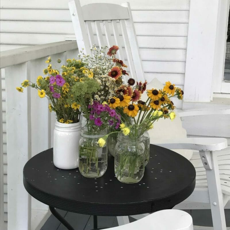 farmhouse front porch with country wildflowers in mason jars for added spring decor
