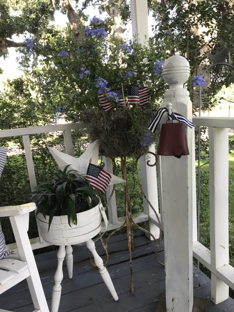 Patriotic decor in plants on farmhouse front porch