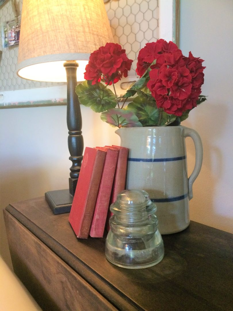 vintage books, old pitcher with red flowers and a vintage insulator for July 4th decor