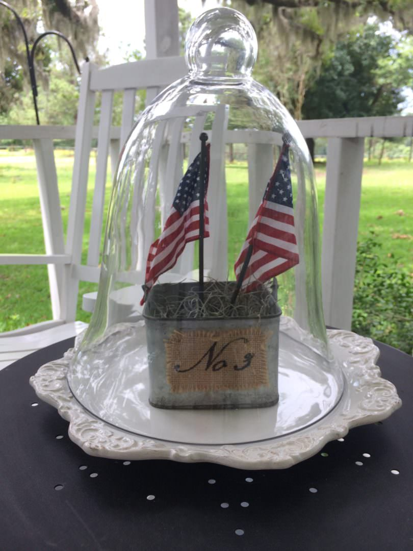 July 4th decor under a glass cloche on a farmhouse front porch