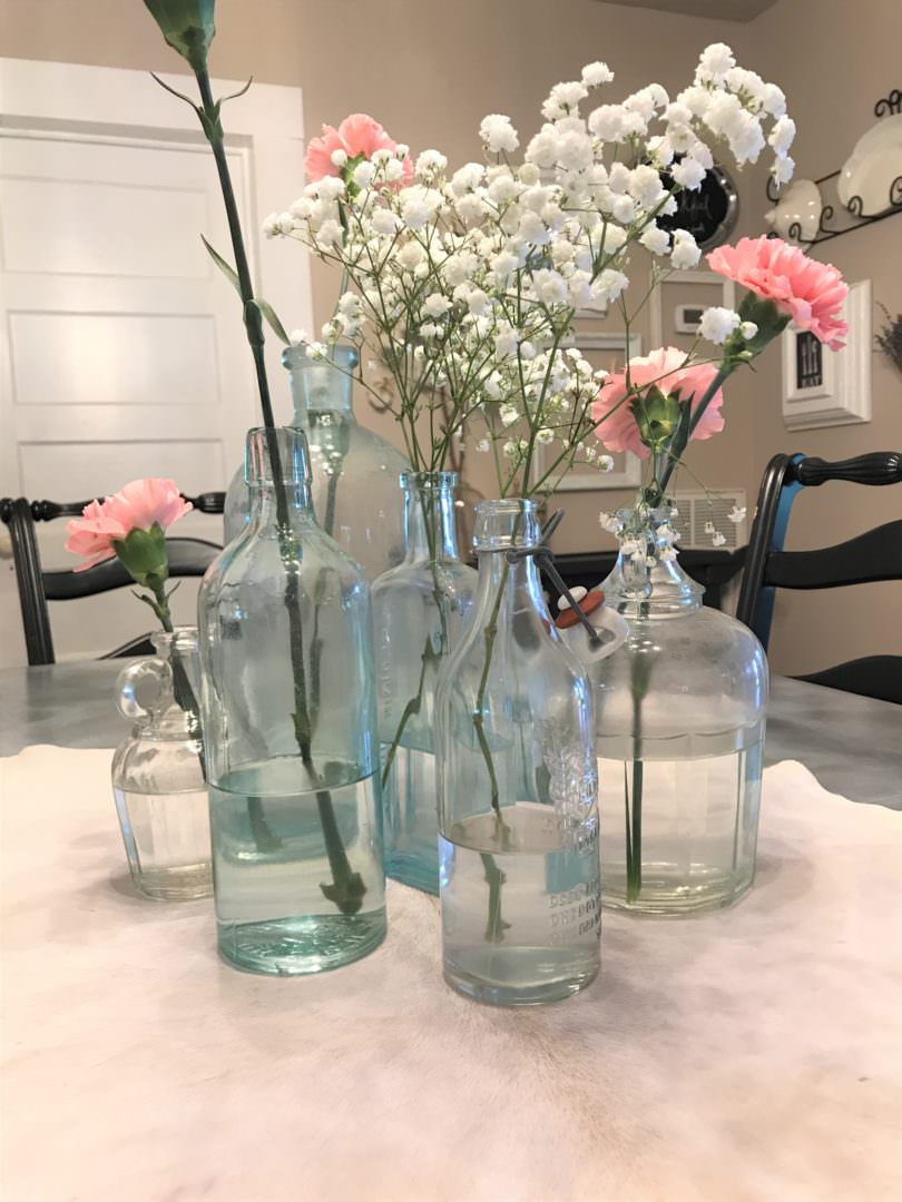 vintage bottles used as an everyday centerpiece on table