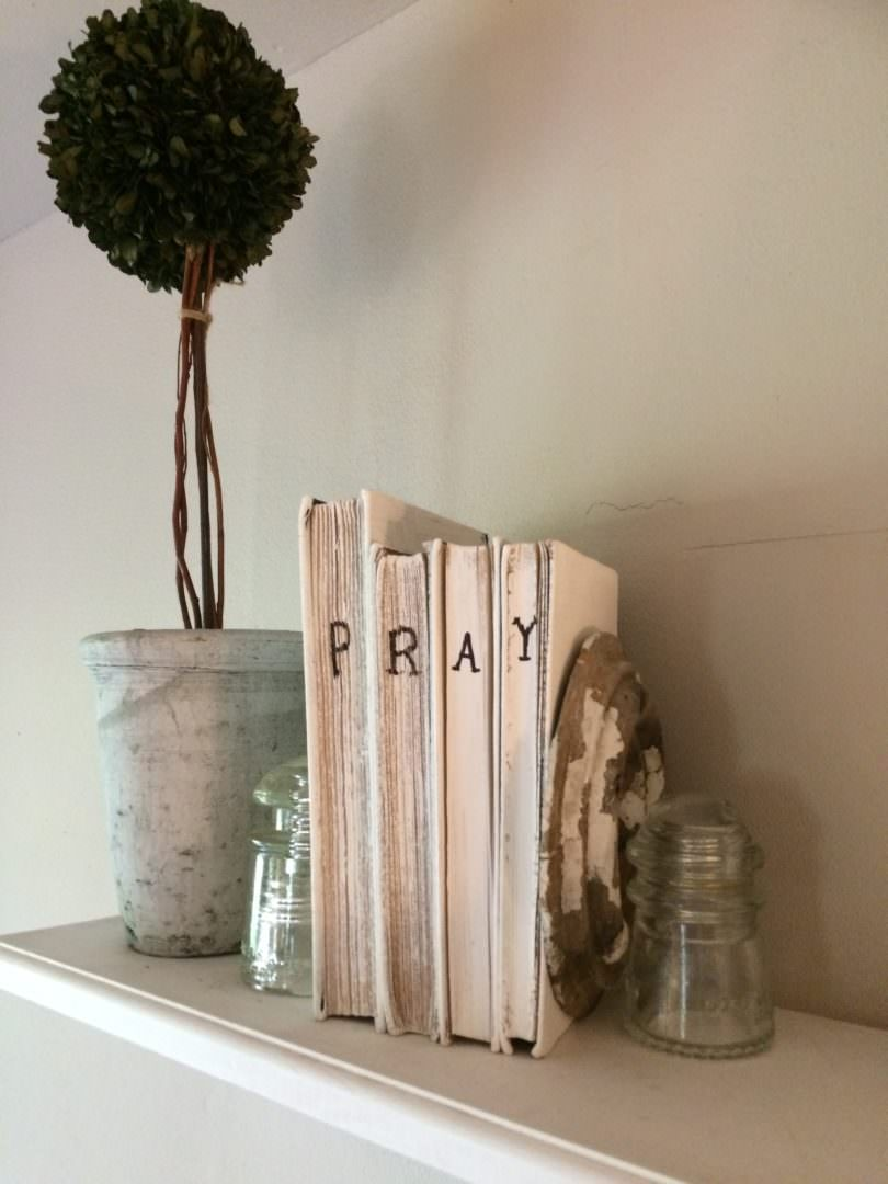 Books that were painted and had the word PRAY wtritten on them with a Sharpie pen for farmhouse decor