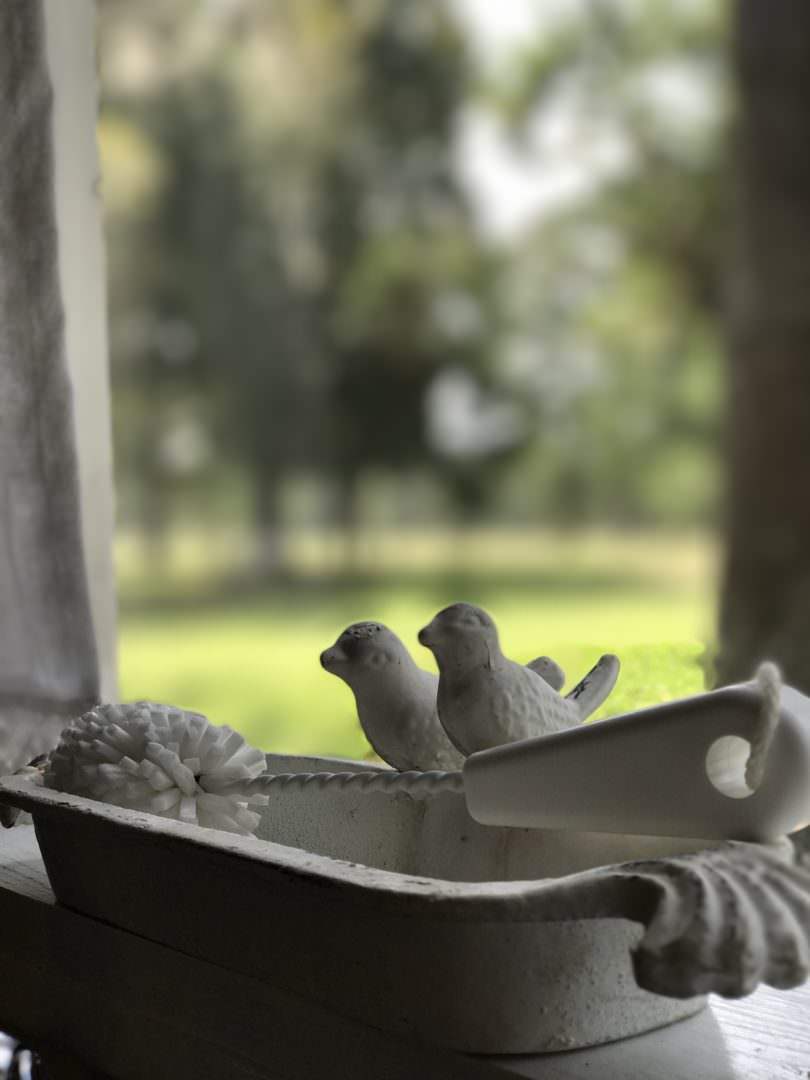 Using a cast iron bird feeder as a sponge holder for farmhouse kitchen details. By CountyRoad407.com