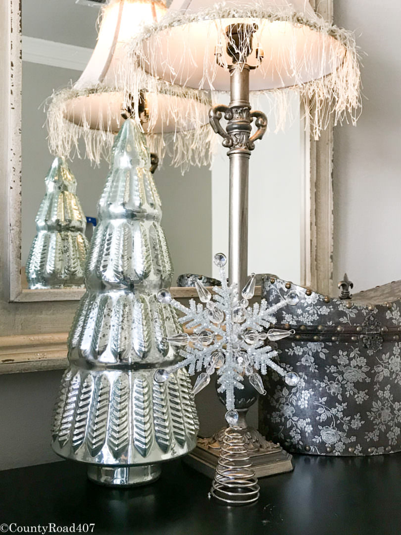Glass trees and a tree topper make inexpensive bed side table Christmas decor. Countyroad407.com