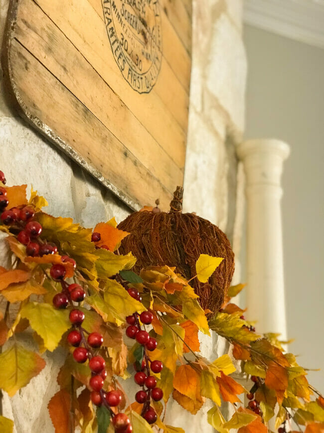 fall mantel with pumpkin and fall leaves and berries