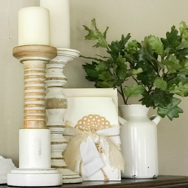 Natural and white candle holders, deconstructed books and white vase with green leaves