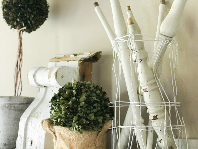 vintage spindles, boxwood greenery and white chippy architectural piece