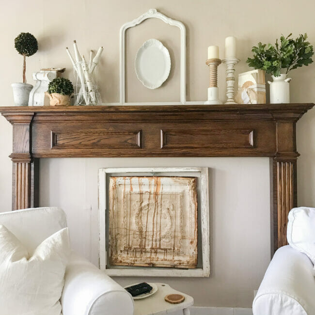 Country style mantelpiece with vintage ceiling panels, window frames and white chairs